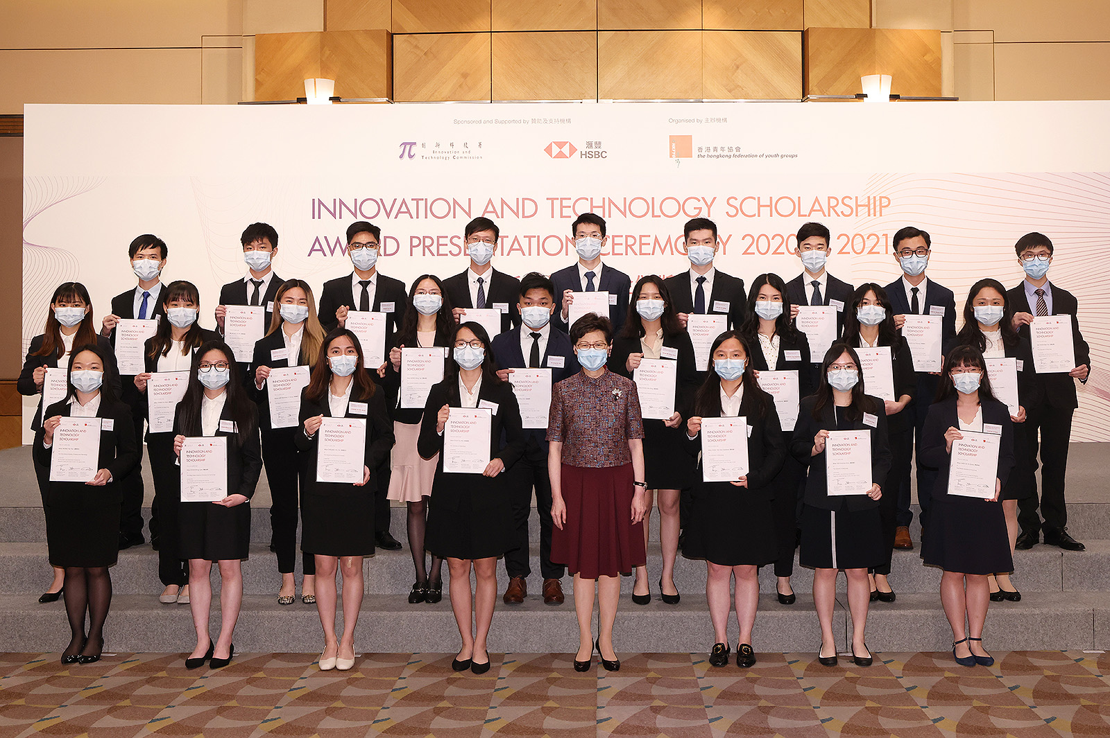 The four CityU awardees, Monica Chan and Harvey Ng (2nd and 5th from left in 2nd row); and Andy Wong and Xavier Yeung (2nd and 3rd from left in 3rd row) received their certificates from the Chief Executive of the HKSAR, Mrs Carrie Lam Cheng Yuet-ngor, at the Innovation and Technology Scholarship Award Presentation Ceremony on 21 June.
