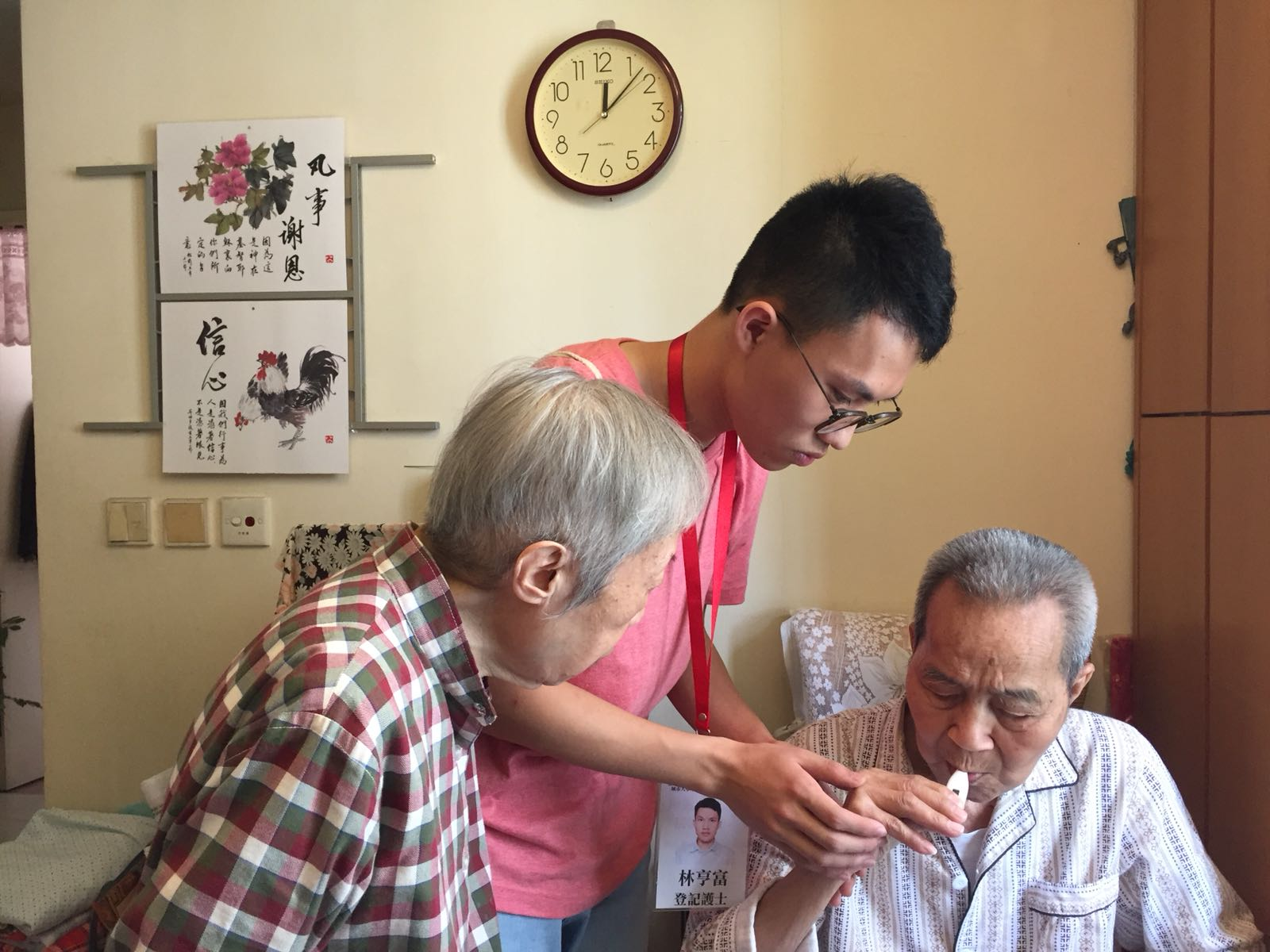 A nurse from the project team (middle) teaches an elderly and his caregiver how to administer medication during home visit.