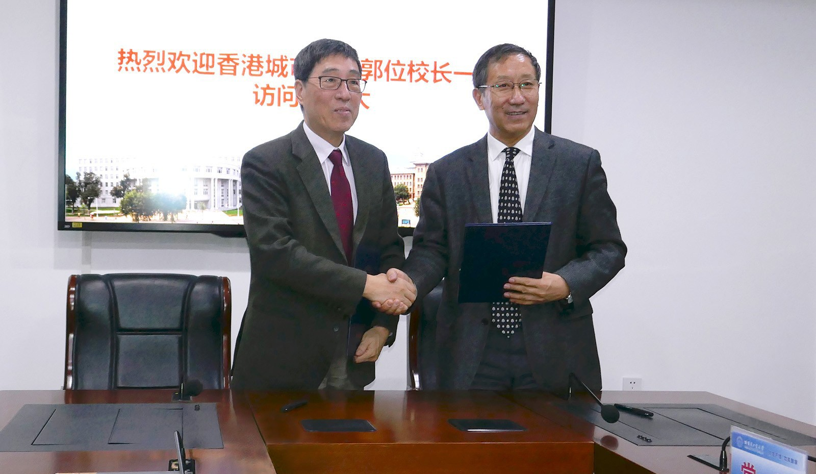 Professor Kuo (left) and Professor Zhou sign the MOU.
