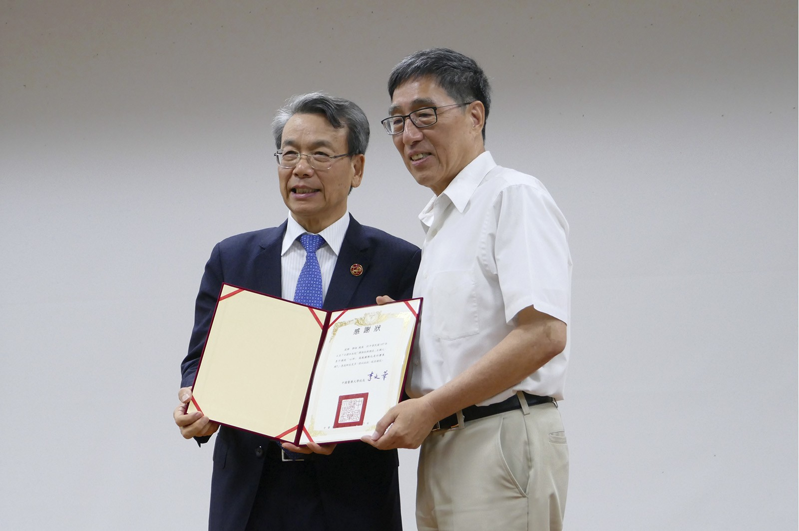 Professor Kuo (right) receives a certificate of appreciation from Professor Lee Wen-hwa, President of CMU.
