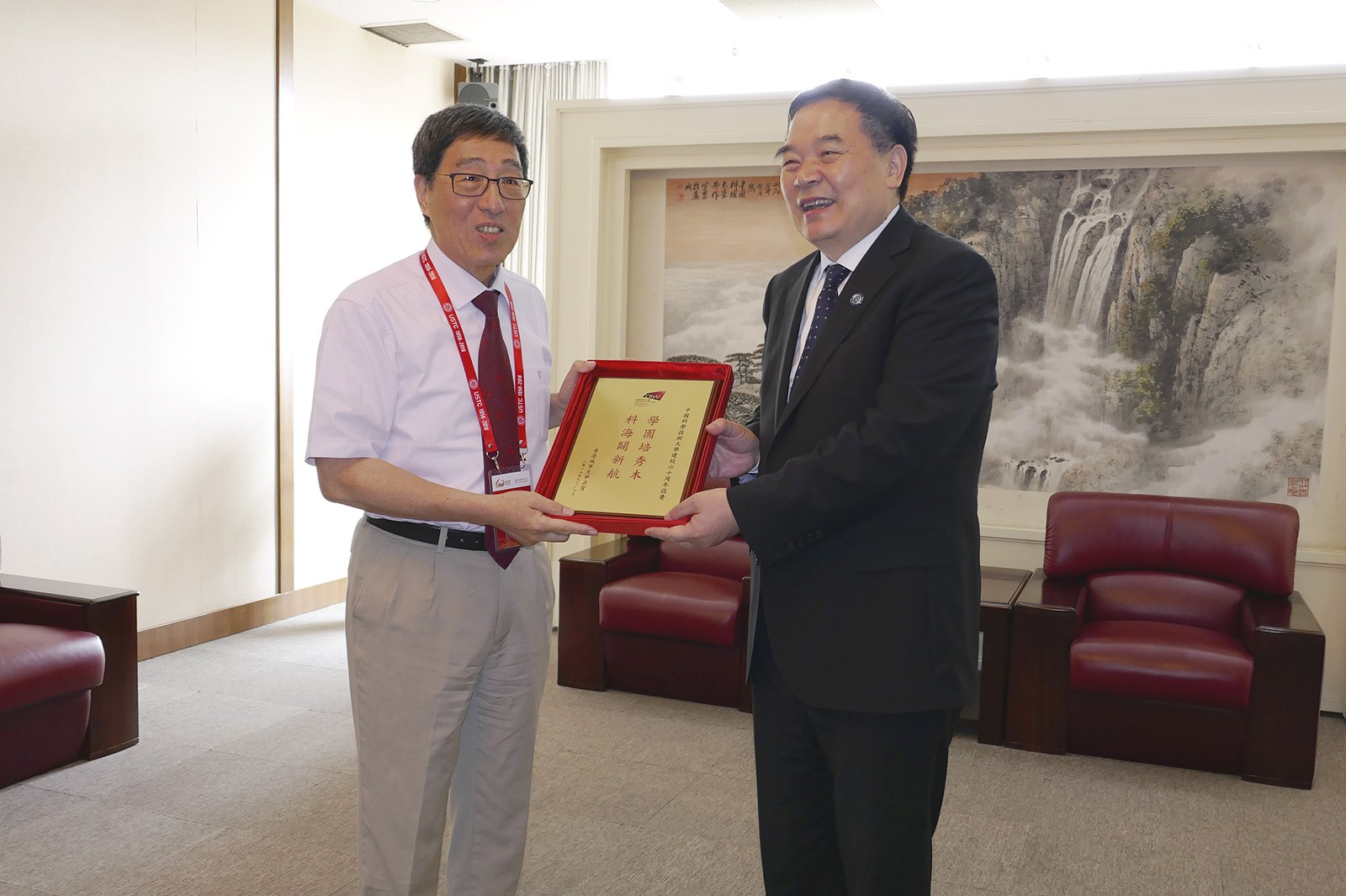 Professor Kuo (left) presents a souvenir to Professor Bao Xinhe, President of USTC.