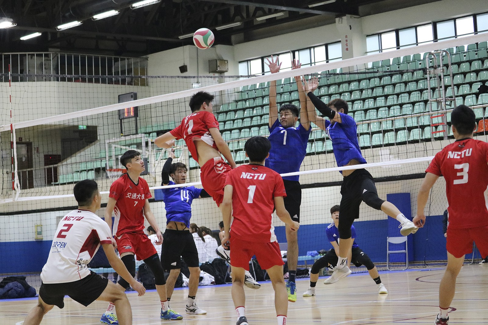 Men's teams from CityU (blue tops) and NCTU (red tops) compete in volleyball. (Photo credit: NCTU)