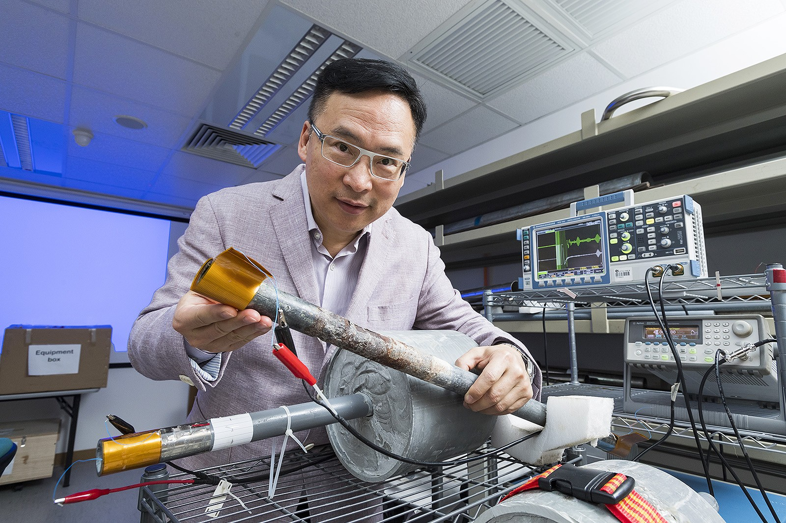 The golden sheet held by Dr Peter Tse Wai-tat is a sensor that, when wrapped around exposed parts of a pipe, identifies corrosion in parts of a pipe that are covered.